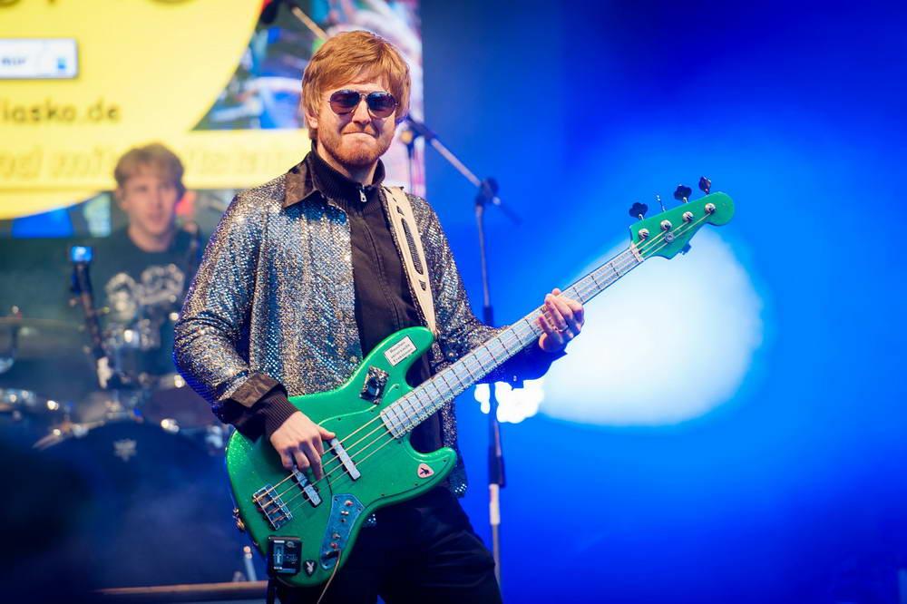 Bassist ,it grünem bass grinst in die Kamera. Im Hintergrund der Schlagzeuger