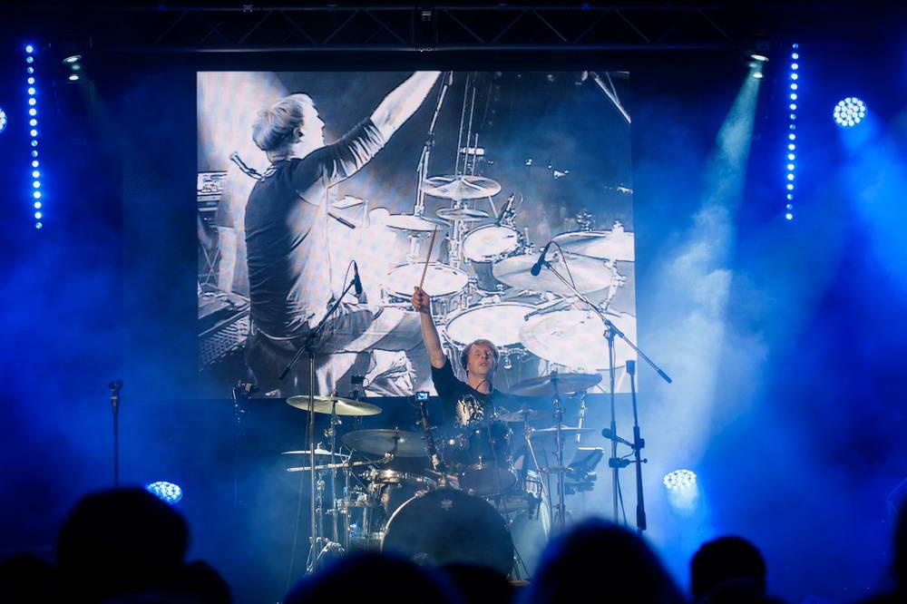 Schlagzeuger beim Drumsolo. Schönes blaues Licht. Im Hintergrund Videoleinwand
