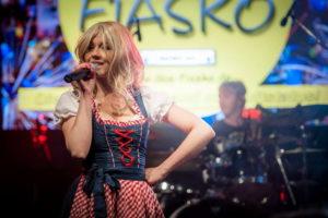 Sängerin im Dirndl lächelt in das Publikum