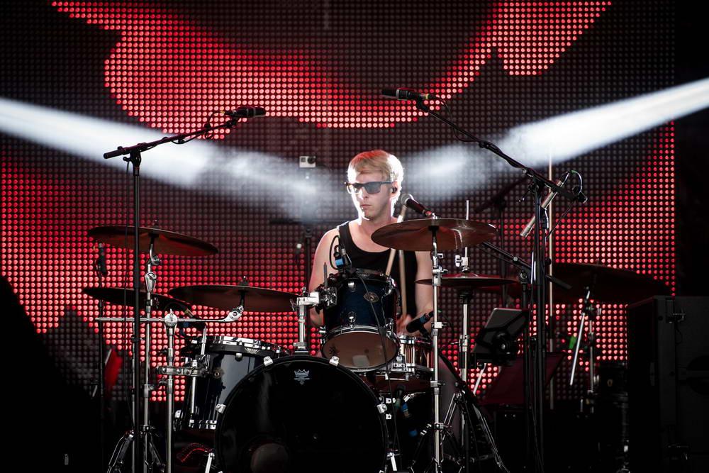 Schlagzeuger mit cooler Sonnenbrille und zwei Lichtspots von den Seiten