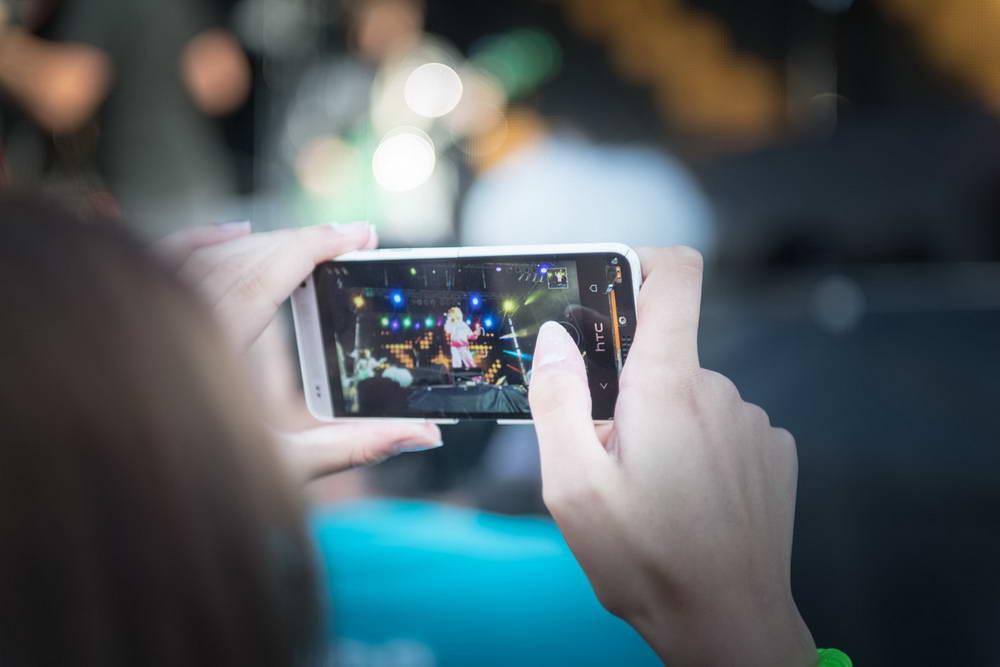 Zuschauer fotografiert mit Handy die band