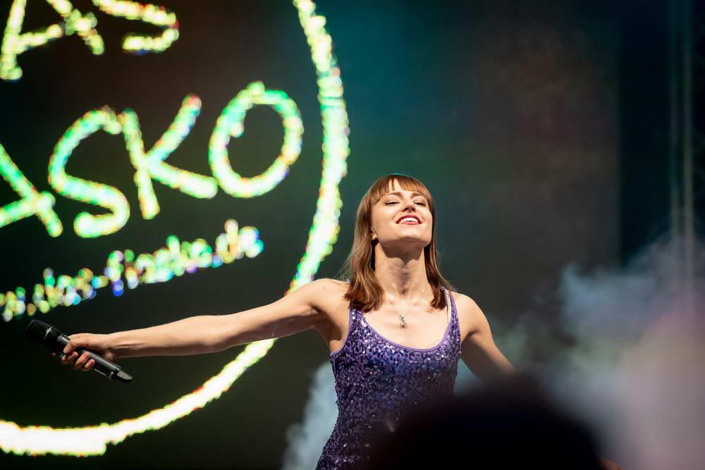 Sänger streckt beide Arme von sich und lächelt in das Publikum