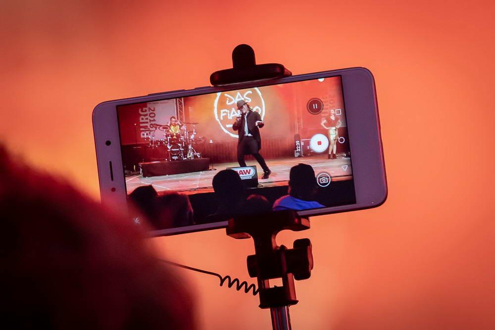 Zuschauen filmt mit Handy die Band