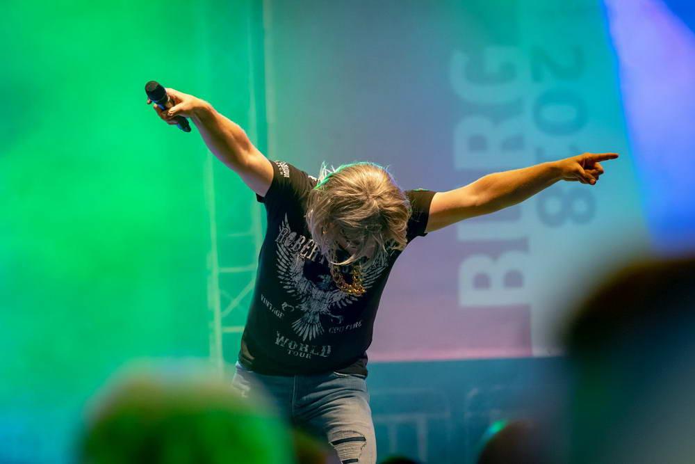 Sänger als Robert Geissen verkleidet mit Mikrofon in der hand hält beide Arme Richtung Publikum