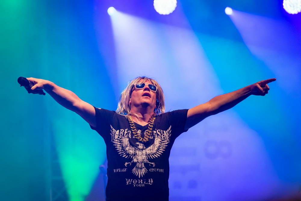 Sänger als Robert Geissen verkleidet mit beiden Armen zur Seite