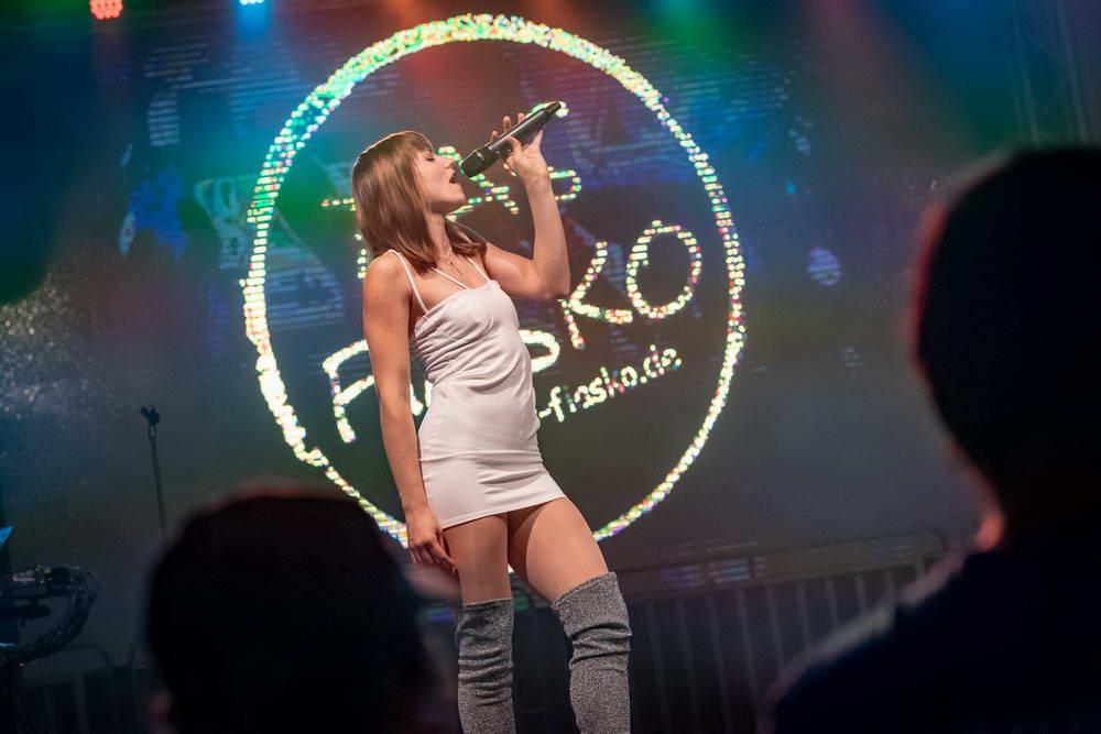 Sängerin im kurzen sexy Kleid als Kylie Minoque steht seitlich zum Publikum
