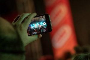 Zuschauer hält Handy hoch und macht Foto von der Band
