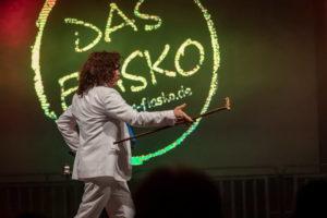 Sänger als Patrick Fernandez verkleidet. Im Hintergrund sieht man das Fiaskologo