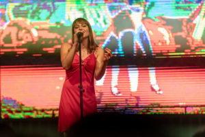 Sängerin in einem pinken Kleid. Im Hintergrund läuft ein Video von dem Song Las Ketchup