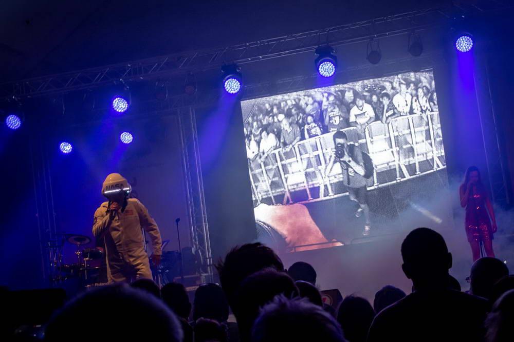 Sänger als Major Tom. Im Hintergrund Leinwand mit Foto von einem Fotografen, der gerade Major Tom fotografiert