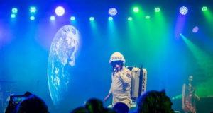 Sänger als Major Tom im Raumfahreranzug. Im Hintergrund auf der Leinwand ist die Erde zu sehen...
