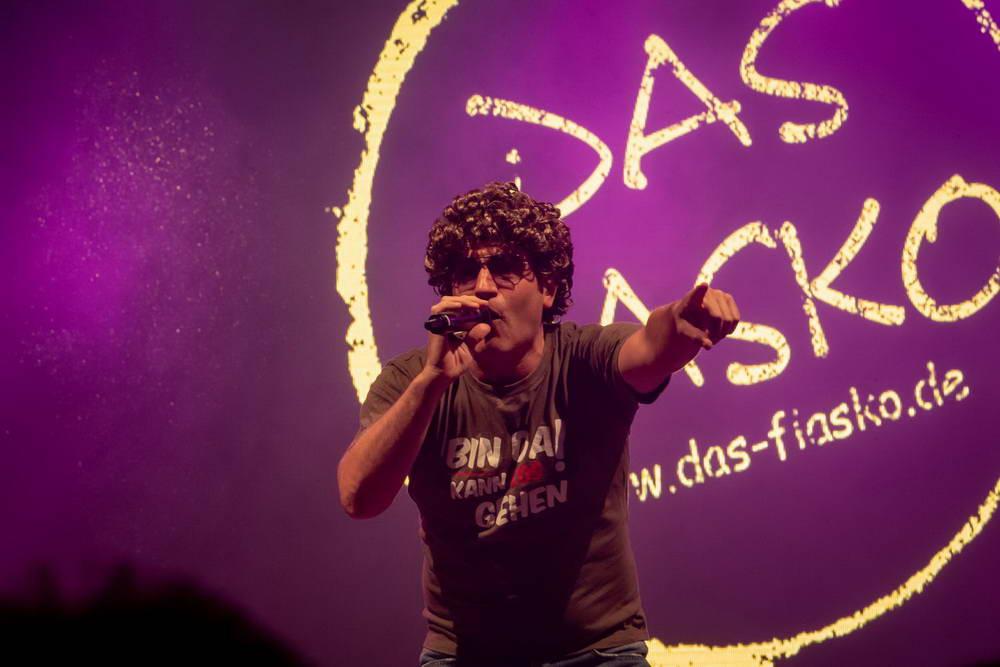 Atze Schröder leicht gebückt mit Blick in das Publikum. Im Hintergrund auf der Leinwand das Fiasko Logo