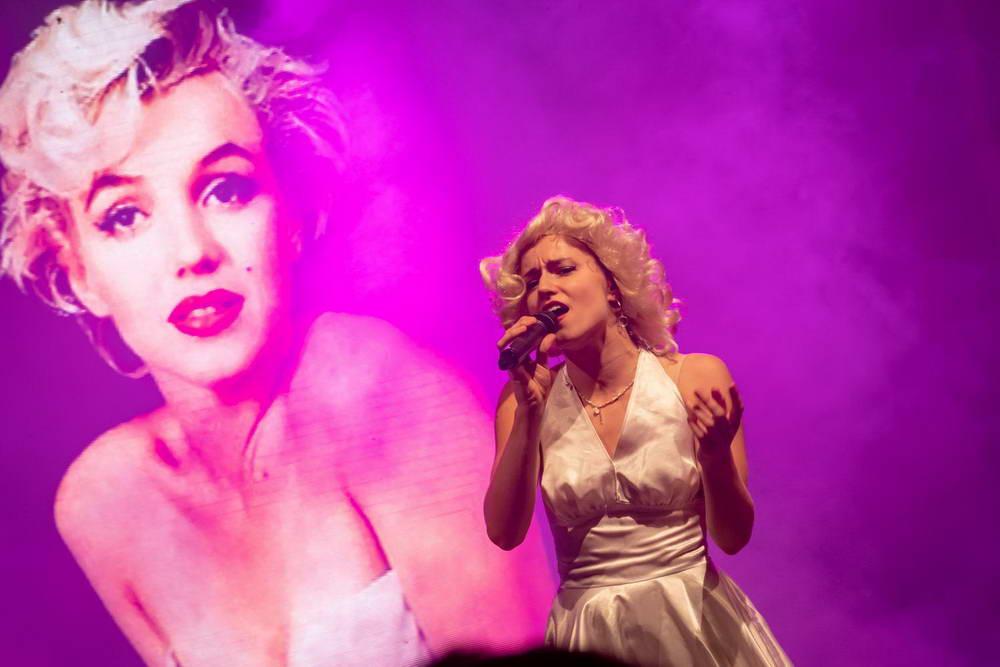 Sängerin als Marylin Monroe vor einer Videoleinwand mit Bild von monroe
