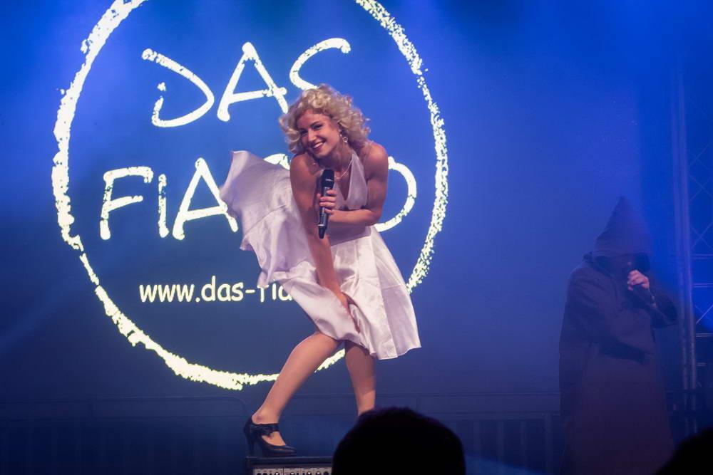 Sängerin macht die berühmte Marylin Monroe Figur. Kleid wird von unten mit Luft nach oben gedrückt.
