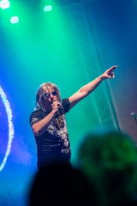Sänger als Robert Geissen verkleidet mit Mikrofon am Mund und Blick Richtung kamera
