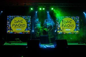 Foto vom Bühnenaufbau. Mitte Schlagzeug, rechts und links davon jeweils eine Leinwand. Auf den Leinwänden ist das Fiaskologo zu sehen.