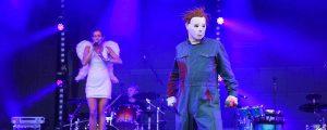 Startseite. Sänger als Mychael Meyers verkleidet. Im Hintergrund Sängerin und Schlagzeuger im blauem LichtTitelbild