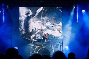 Schlagzeuger spielt Drumsolo. Im Hintergrund eine Videoleinwand mit Video von dem Schlagzeuger