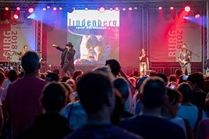 Sänger als Udo Lindenberg verkleidet mit Publikum im Vordergrund