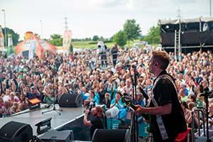 Sänger von der Bühne aus fotografiert mit Publikum im Hintergrund