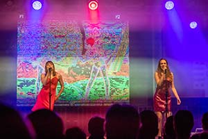 Zwei Sängerinnen nebeneinander die den Song Las Ketchup singen. Im Hintergrund läuft ein Video auf einer großen Leinwand.