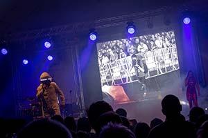 Foto aus dem Publikum. Auf der Bühne große Leinwand die Publikum zeigt
