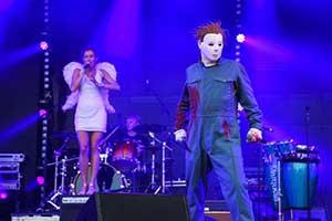Sänger als Michael Meyers mit blauem, blutverschmierten Anzug an. Im Hintergrund ein Engel auf eine Box. Gespielt wird dabei der Titel Engel von Rammstein