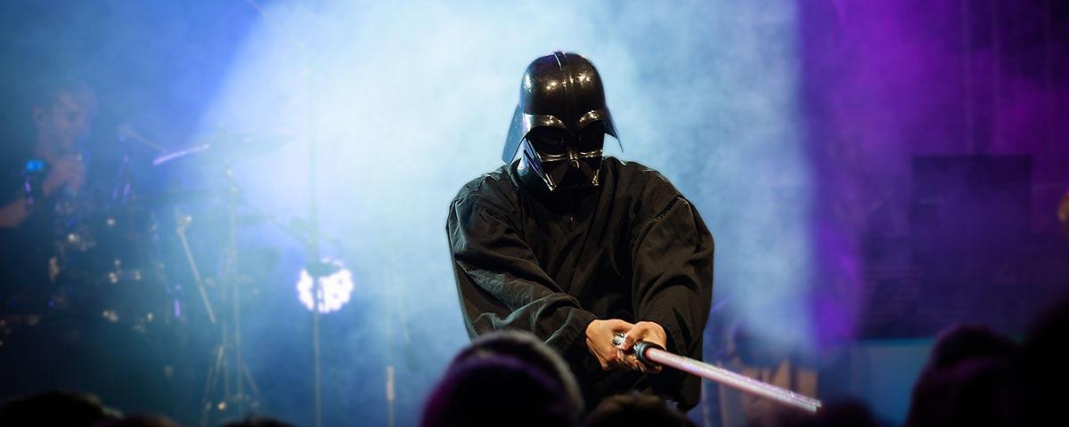 Titelbild Downloads. Sänger als Darth Vader mit Schwert