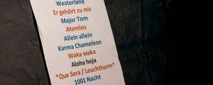 Titelbild Songliste. Setliste hängt an einer schwarzen Zeltwand.