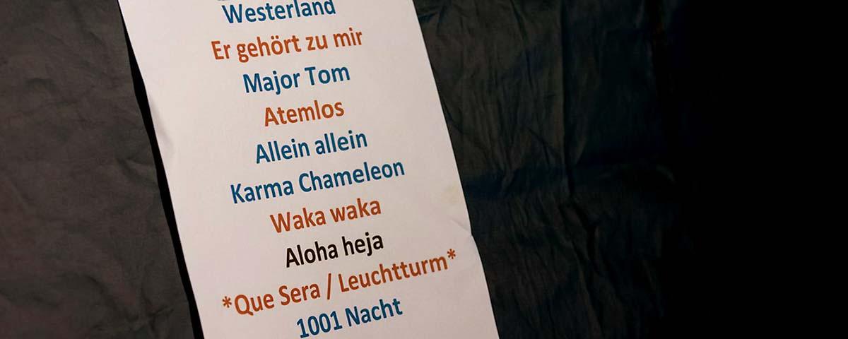 Titelbild. Setliste hängt an Zeltwand schwarzer Zeltwand.
