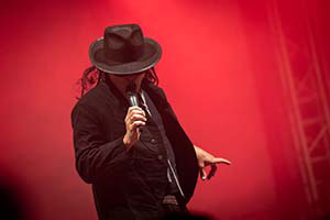 Sänger als Udo Lindenberg un rotem Licht auf der Bühne