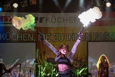 Sängerin als Lara Croft hält zwei Pistolen nach oben, aus denen ein Knalleffekt mit Rauch aufsteigt
