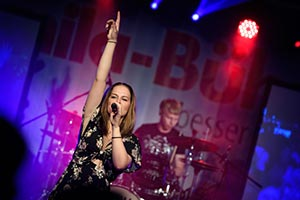 Sängerin im schwarzem Kleid mit Schlagzeuger im Hintergrund