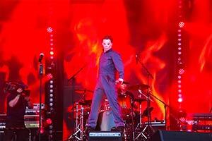 Sänger verkleidet als Michael Meyers steht auf einer Box im rotem Bühnenlicht
