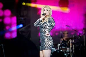 Sängerin im silbernem Glitzerkleid steht seitlich zum Publikum auf großer Bühne