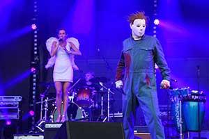 Sänger verkleidet als Michael Meyers. Im Hintergrund Sängerin als Engel verkleidet. Blaues Bühnenlicht