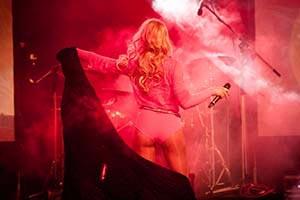 Sängerin im sexy pinkem Anzug im rotem Bühnenlicht