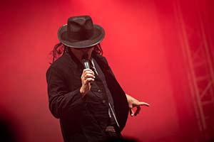 Sänger als Udo Lindenberg verkleidet im rotem Bühnelicht