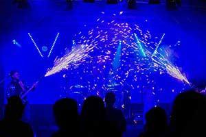 Pyrotechnik von den Seiten Richtung Bühnenmitte im blauem, dunklem Bühnenlicht