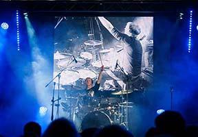 Schlagzeuger bei Solo, Hinter dem Schlagzeuger riesige Leinwand