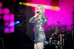 Sängerin im silbernem Kleid steht seitlich zur Bühne