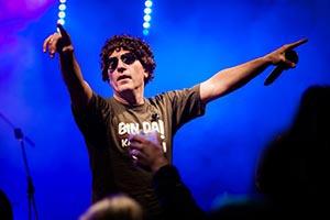 Unser Sänger als Atze Schröder verkleidet hebt beide Arme Richtung Publikum