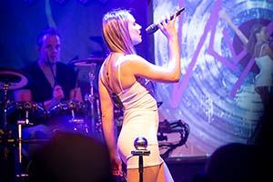 Sängerin im kurzem, weissem Kleid steht seitlich zum Publikum. Im Hintergrund der Schlagzeuger