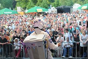 Sänger im Raumfahreranzug von der Bühne aus fotografiert. Im Hintergrund das Publikum