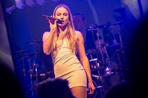 Sängerin im weisem, kurzem Kleid. Im Hintergrund der Schlagzeuger, blaues Bühnenlicht