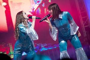 Beide Sängerinnen als Abba verkleidet im rotem Bühnenlicht. Band auf einem Stadtfest