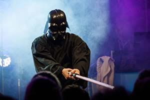 Sänger im Darth Vader Kostüm häl Schwert Richtung Publikum