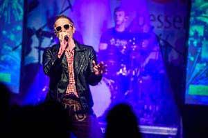 Sänger als Andreas Gabalier verkleidet im blauem Bühnenlicht. Partyband in Mölln