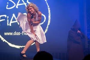 Sängerin im weissem Marily Monroe Kleid steht auf einer Box. Kleid fliegt nach oben. Blaues Bühnenlicht. Stadtfest in Hamburg
